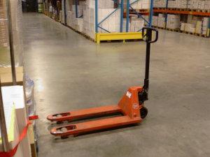 Оранжевая гидравлическая тележка на маленьких колесиках